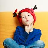 Niño pequeño en sombrero rojo del reno del invierno en casa Imagen de archivo