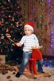 Niño pequeño en un casquillo de Santa Claus que monta un juguete del reno Fotografía de archivo libre de regalías