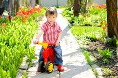 Niño pequeño en un children& x27; bicicleta de s fotos de archivo libres de regalías