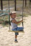 Niño pequeño en un oscilación Fotografía de archivo