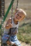 Niño pequeño en un oscilación Fotos de archivo libres de regalías