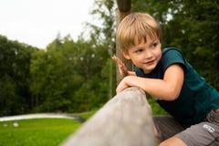 Niño pequeño en un primer verde del parque Fotos de archivo