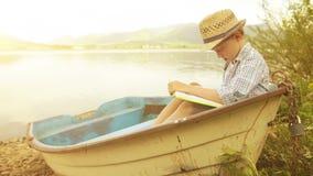 Niño pequeño en un sombrero de paja que se sienta en el barco rústico que lee un libro almacen de metraje de vídeo