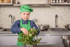 Niño pequeño en un sombrero del ` s del cocinero y delantal en la cocina Fotografía de archivo libre de regalías