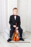 Niño pequeño en un traje que se sienta con el violín fotografía de archivo libre de regalías