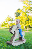 Niño pequeño en un unicornio del juguete Campo herboso en el parque Árbol en campo sonrisa y he& x27 del muchacho; s feliz imagen de archivo libre de regalías
