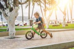 Niño pequeño en una bici de la balanza Cogido en el movimiento, en una calzada P fotos de archivo