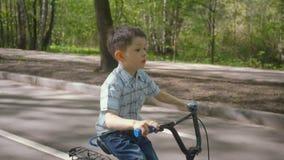 Niño pequeño en una bicicleta en la carretera de asfalto Muchacho lindo que aprende montar la bicicleta en una pista de la bicicl almacen de video