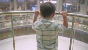 Niño pequeño en una cabina de cristal del elevador en centro comercial almacen de video