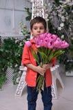 Niño pequeño en una camisa roja y un ramo de tulipanes Fotografía de archivo