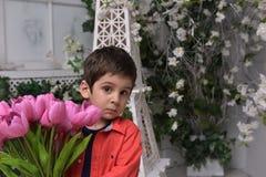 Niño pequeño en una camisa roja y un ramo de tulipanes Fotos de archivo