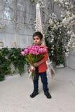 Niño pequeño en una camisa roja y un ramo de tulipanes Imagen de archivo