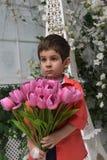 Niño pequeño en una camisa roja y un ramo de tulipanes Imagen de archivo libre de regalías