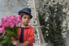 Niño pequeño en una camisa roja y un sombrero con un ramo Fotografía de archivo libre de regalías