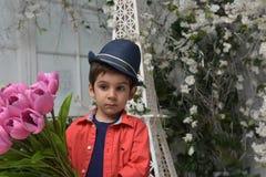 Niño pequeño en una camisa roja y un sombrero con un ramo Imagen de archivo libre de regalías