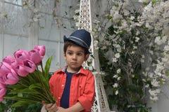 Niño pequeño en una camisa roja y un sombrero con un ramo Imágenes de archivo libres de regalías