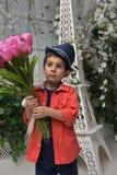 Niño pequeño en una camisa roja y un sombrero con un ramo Fotos de archivo