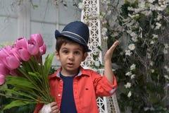 Niño pequeño en una camisa roja y un sombrero con un ramo de tulipanes adentro Foto de archivo libre de regalías