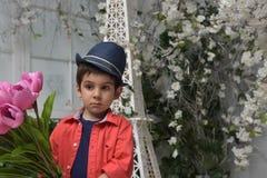 Niño pequeño en una camisa roja y un sombrero con un ramo de tulipanes adentro Fotos de archivo libres de regalías