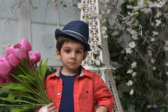 Niño pequeño en una camisa roja y un sombrero con un ramo de tulipanes adentro Foto de archivo