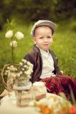 Niño pequeño en una chaqueta y los pantalones de tela escocesa a sentarse en el amortiguador, ne Imágenes de archivo libres de regalías