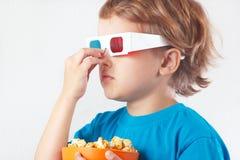 Niño pequeño en vidrios estéreos con el cuenco de palomitas Imágenes de archivo libres de regalías