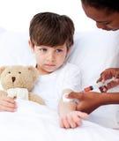 Niño pequeño enfermo que recibe una inyección Imagen de archivo