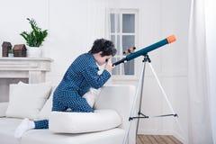 Niño pequeño enfocado que mira a través del telescopio Imagen de archivo libre de regalías
