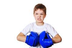 Niño pequeño enojado en guantes de boxeo azules fotografía de archivo