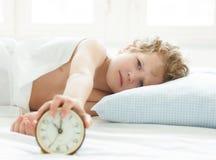 Niño pequeño enojado que miente en la cama y que para el despertador por mañana Imagenes de archivo