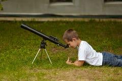 Niño pequeño feliz con el telescopio Imagen de archivo