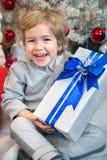 Niño pequeño feliz con la caja de regalo de vacaciones Imagen de archivo