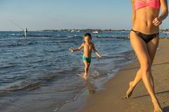 Niño pequeño feliz con la madre hermosa joven que corre el verano b Foto de archivo