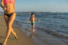 Niño pequeño feliz con la madre que corre en la playa del verano H positivo Foto de archivo