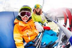 Niño pequeño feliz con la mamá, elevación de silla del esquí de la montaña Foto de archivo libre de regalías