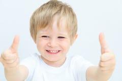 Niño pequeño feliz con los pulgares para arriba en blanco Foto de archivo