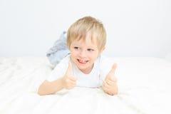 Niño pequeño feliz con los pulgares para arriba en blanco Imágenes de archivo libres de regalías