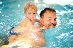 Niño pequeño feliz con su padre en piscina Fotos de archivo libres de regalías