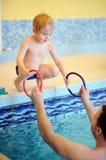 Niño pequeño feliz con su padre que hace ejercicio en piscina Imagen de archivo