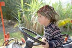 Niño pequeño feliz de dos años que se divierten en el tractor en verano Imagenes de archivo