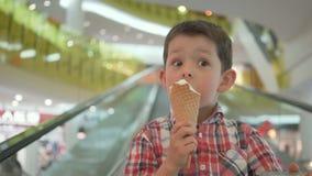 Niño pequeño feliz en carro de la compra con helado sabroso durante compras de la familia en hipermercado almacen de video