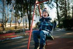 Niño pequeño feliz en el oscilación en día de invierno hermoso Fotos de archivo