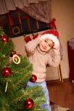 Niño pequeño feliz en un casquillo de Papá Noel que se coloca cerca de un Christm Foto de archivo