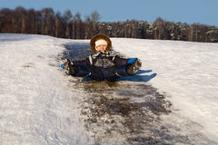 Niño pequeño feliz en una colina del hielo Foto de archivo