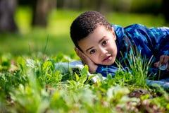 Niño pequeño feliz lindo que miente en hierba verde el la primavera imágenes de archivo libres de regalías