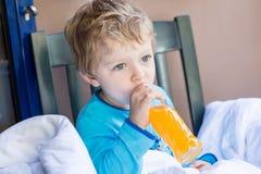 Niño pequeño feliz que bebe el zumo de naranja en balcón Imagenes de archivo