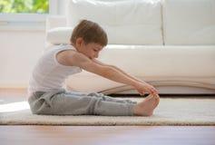 Niño pequeño feliz que ejercita en casa foto de archivo libre de regalías