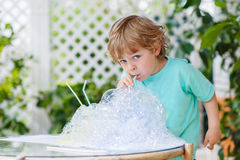 Niño pequeño feliz que hace el experimento con agua y el jabón coloridos Imagenes de archivo