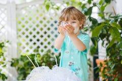 Niño pequeño feliz que hace el experimento con agua y el jabón coloridos Fotografía de archivo