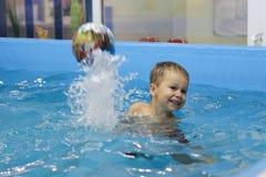 Niño pequeño feliz que juega con la bola en la piscina fotografía de archivo libre de regalías